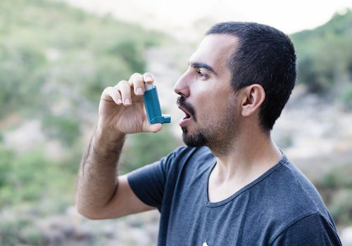 A man using his inhaler on a hike