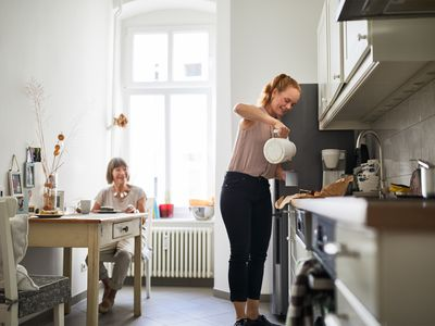 Woman preparing coffee for senior woman at dining table