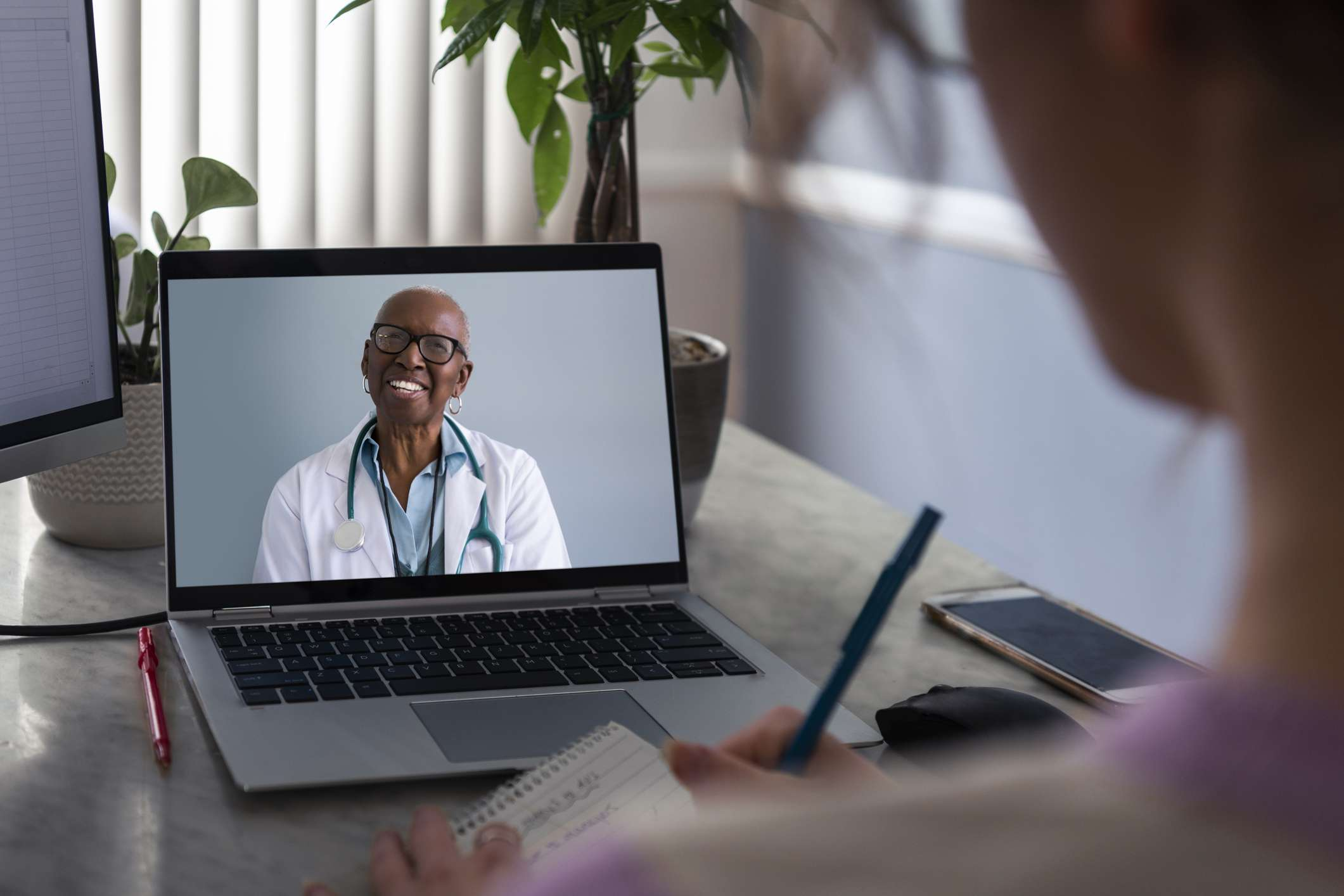 A woman talking to doctor on a video call on a laptop