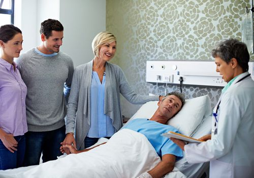 Shot of doctors talking to a man in a hospital bed while his family looks on