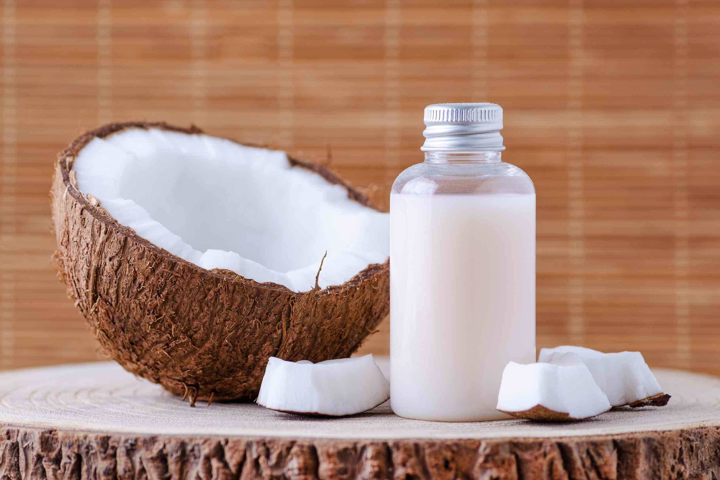 A clear bottle with white liquid next to half a coconut.