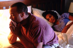 man sitting on edge of bed while woman lays down