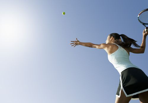 woman throwing a tennis ball into the air to serve it