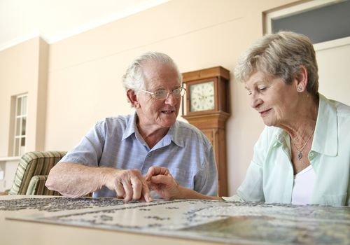 elderly couple doing puzzles