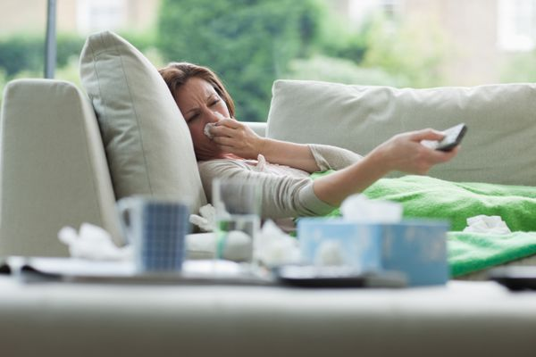 Sick woman laying on sofa holding remote control.