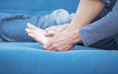 A man massaging his aching foot