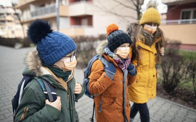 Three children walking with winter gear and face masks.