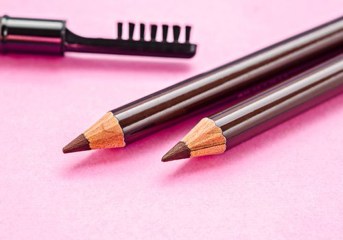 Eyebrow pencils and a brush