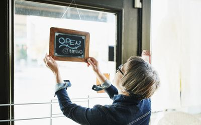 Female business owner turning open sign on door before opening boutique