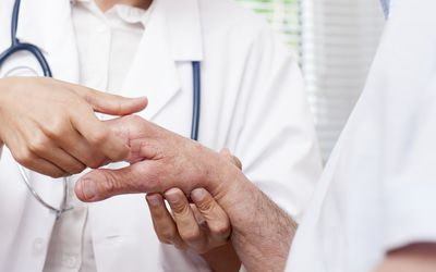 Nurse checking mans hand joints