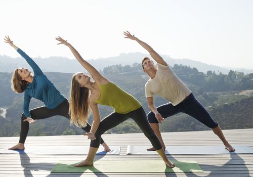 Three people doing yoga on a porch