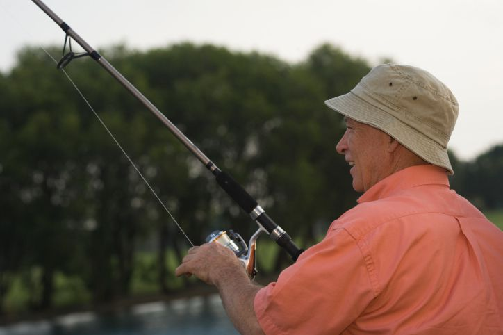 A retired man fishing on a lake