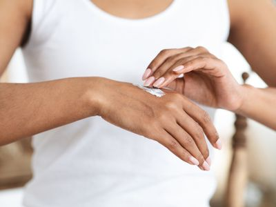 African-American woman applies a patch of cream to her hand.