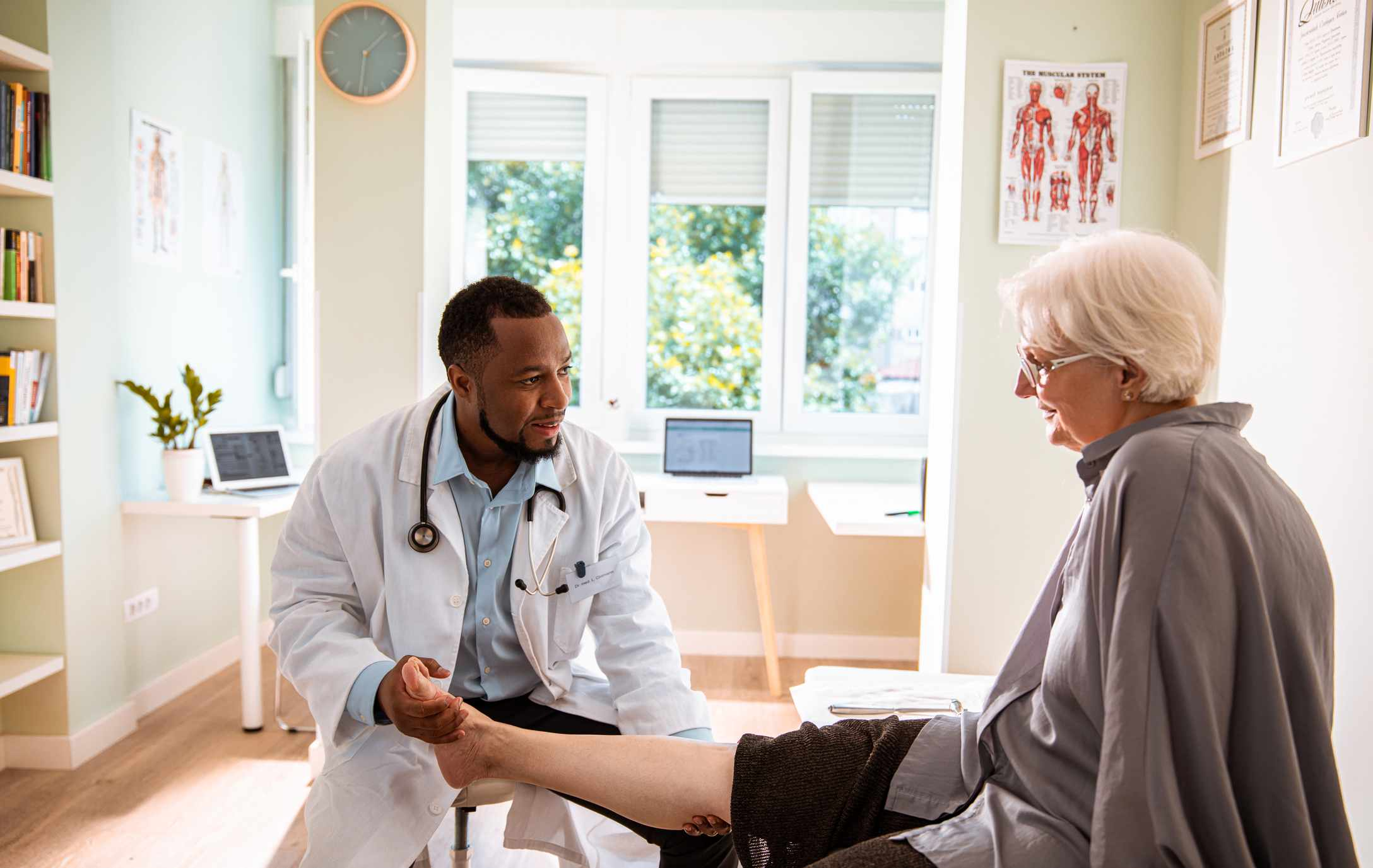 Doctor examines senior woman's leg.