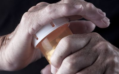 Close up of senior opening a pill bottle