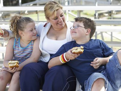 A mother eating in a park with her two children