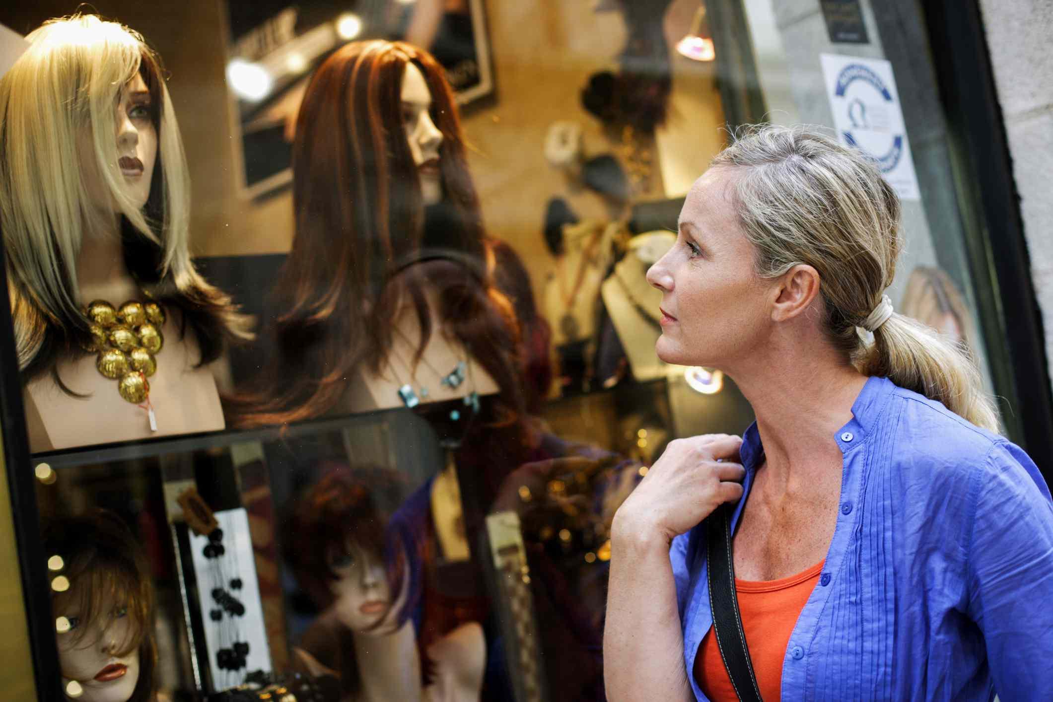 Woman looking in wig shop window