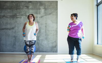 Two women working out together, smiling