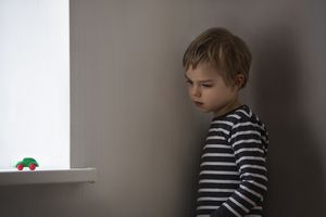 young boy looking at toy car on windowsill