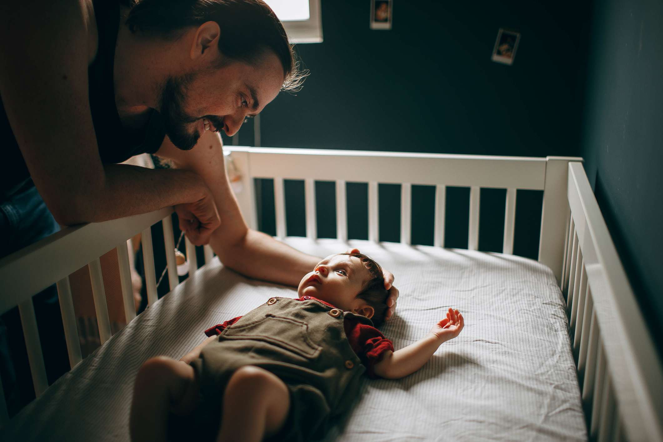 Father interacting with his baby boy laying in a crib