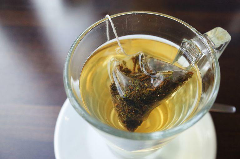 Tea steeps in a glass mug.
