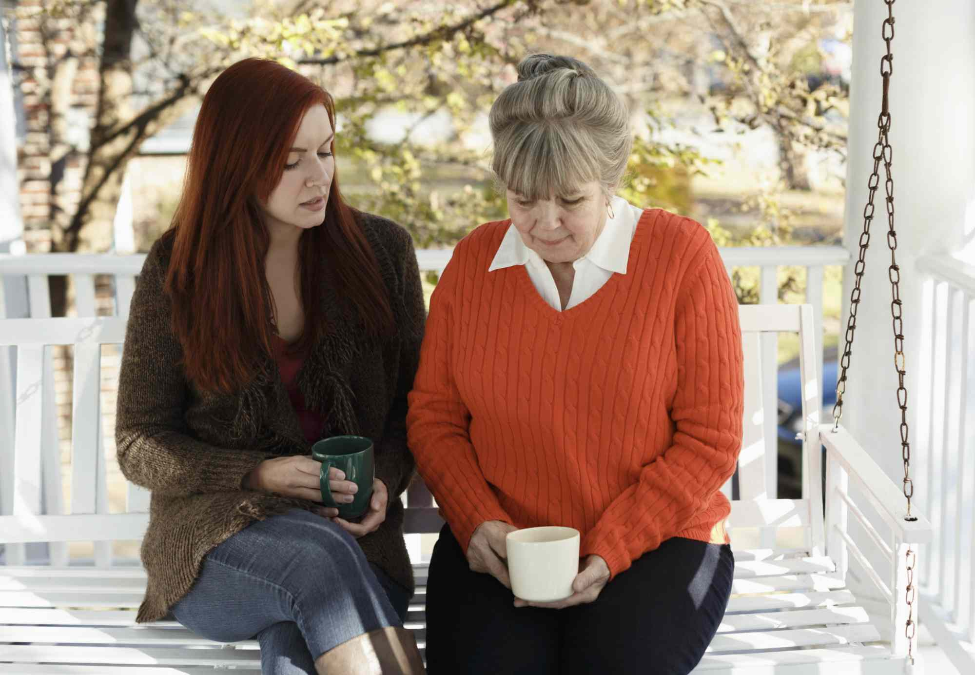 Woman and mature woman sitting on a porch swing, both distressed