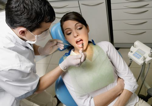 Dentist examining a woman's teeth.