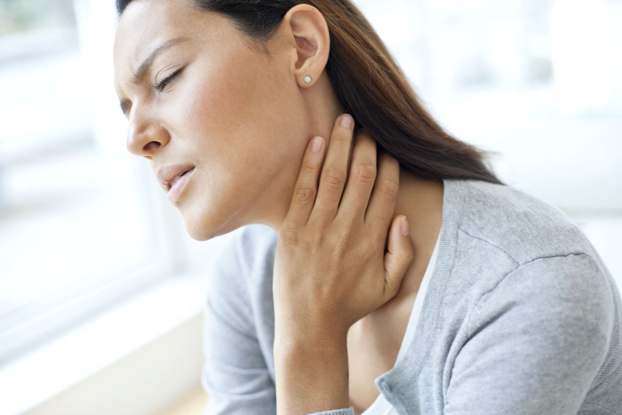 A woman in pain clutching the side of her neck