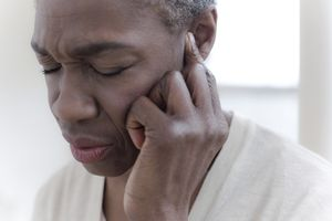 Older Black woman touching her hear with a painful expression on her face.