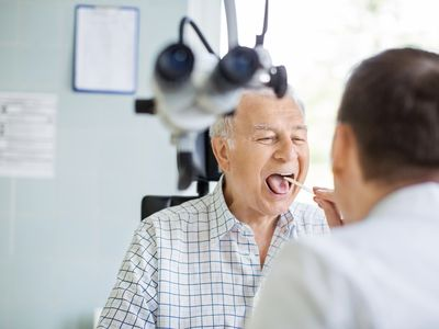 Doctor examines older patient with tongue depressor