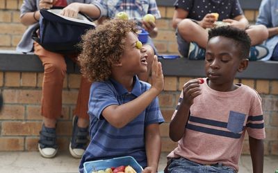 Two young boys at school playing with fruit and being silly