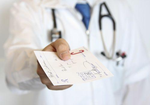 A doctor handing his patient a prescription