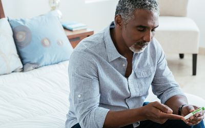 a man checking his blood sugar in the bedroom