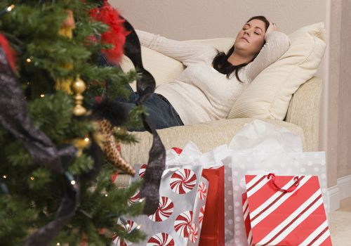 Woman laying on sofa behind a christmas tree and gift bags