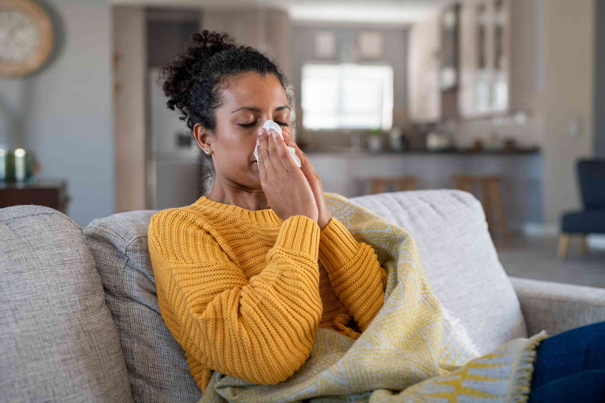 Portrait of young black woman sneezing in to tissue at home. Sick african woman wrapped in blanket sitting on sofa blowing her nose at home. Ill girl sneezing with runny nose in winter.