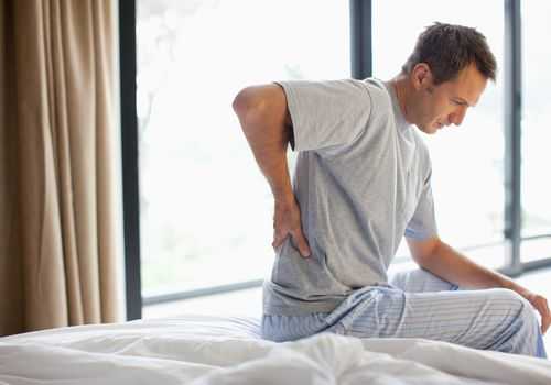 Man with lower back pain sitting on bed