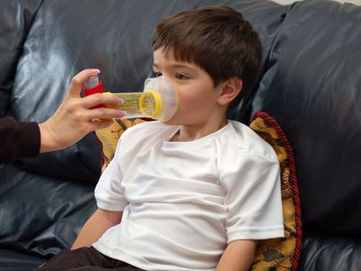 A child using an albuterol MDI with a spacer and mask, which can help relieve asthma symptoms.