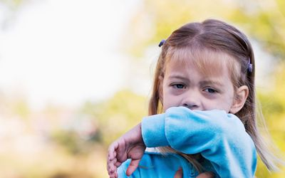 A toddler girl has her right hand on her chest as she coughs into the inside of her left elbow.