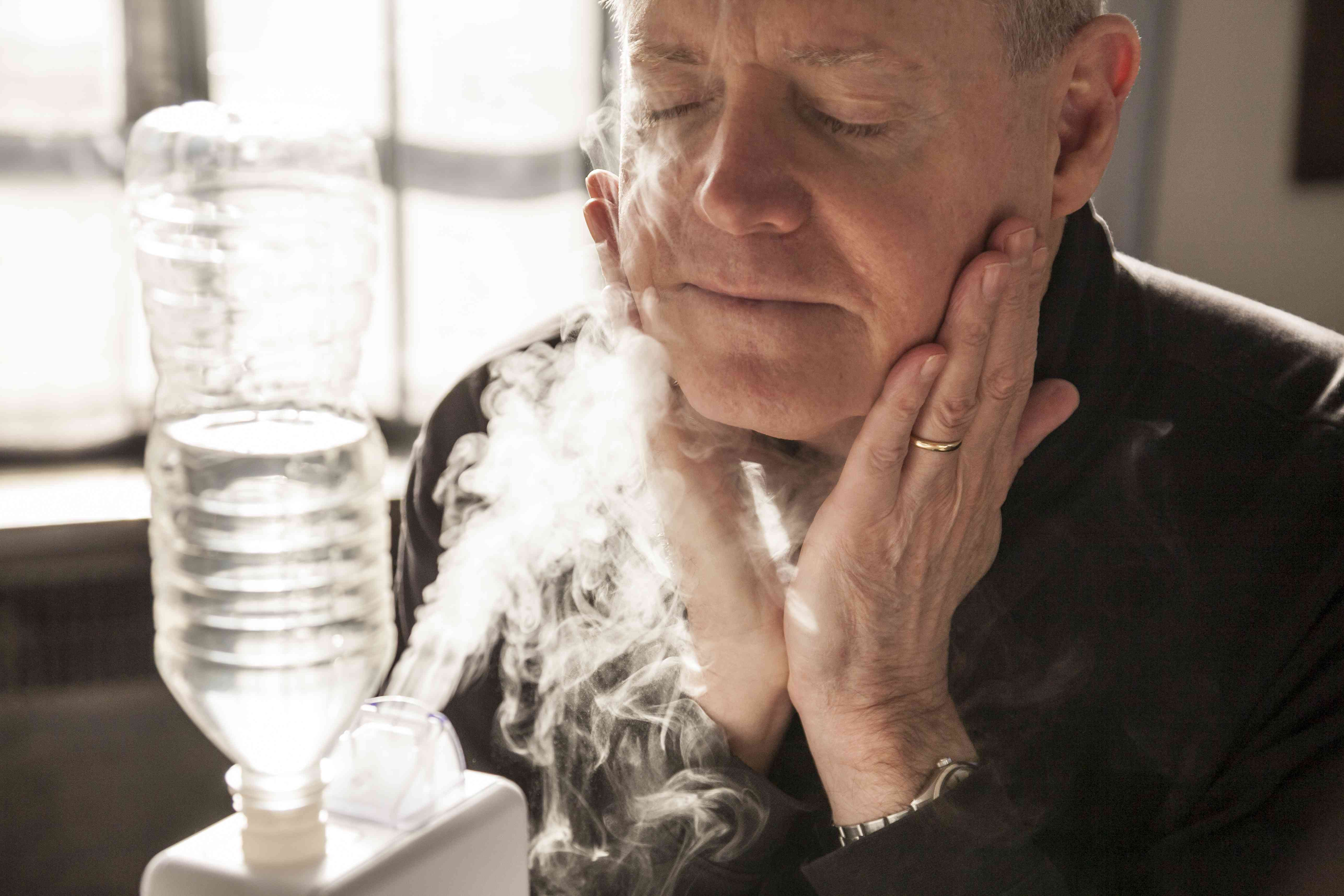 Mature man hydrates with home humidifier