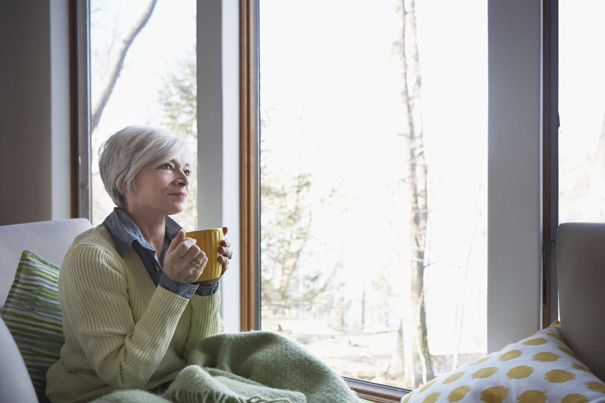 Older adult looking out of a large window while holding a mug