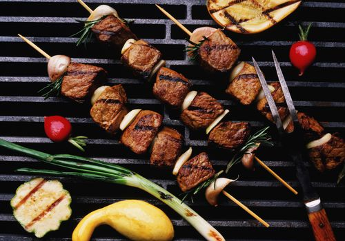 Skewers on a grill with squash and onions