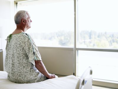 male hospital patient sitting on edge of bed