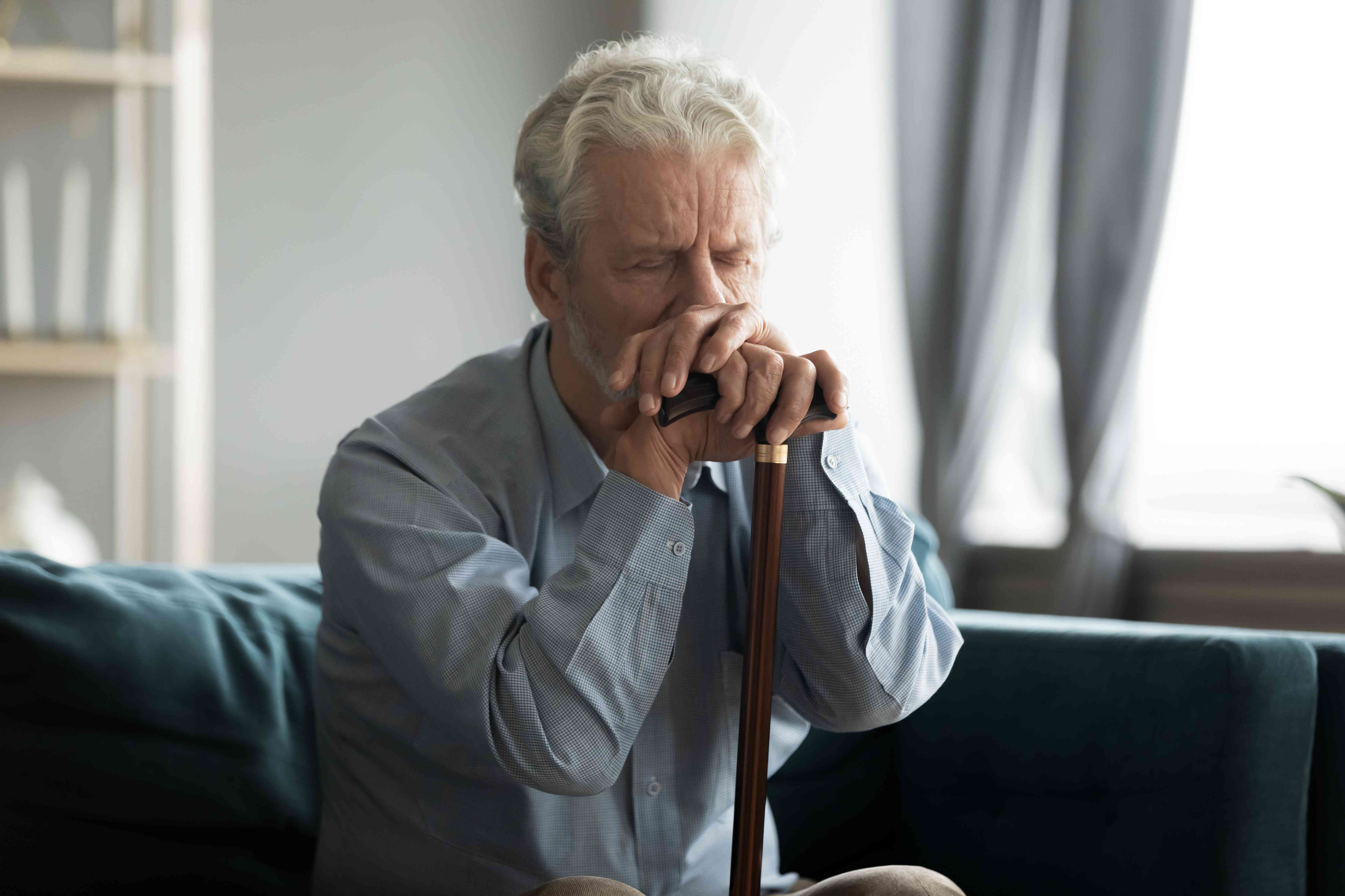 Depressed disabled retired man sitting on couch with cane stick