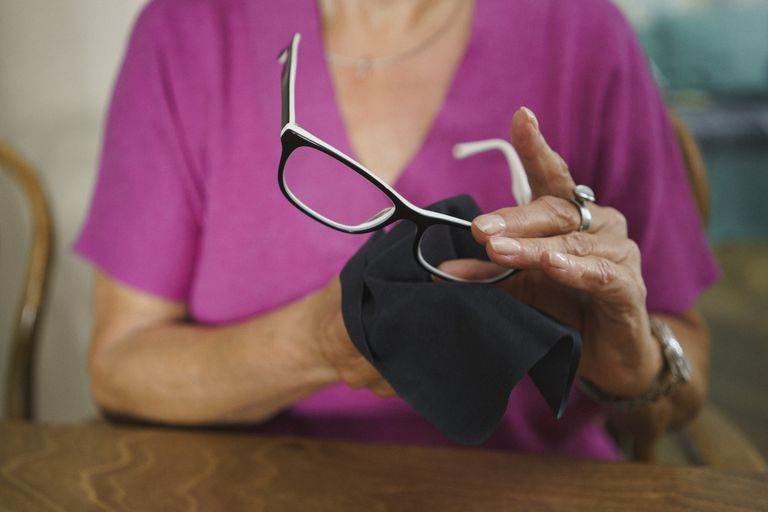 A woman repeatedly cleaning her glasses