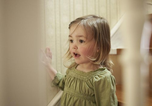 Little girl standing near the stairs.