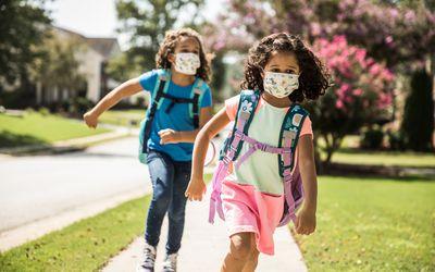 Kids running while wearing face masks.