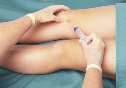 doctor performing a Knee injection on patient