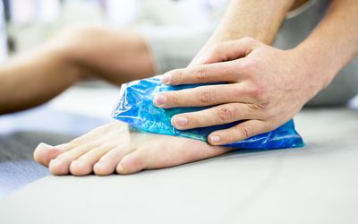 Young man holding ice pack on ankle