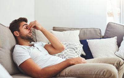 Cropped shot of a young man holding his nose while lying on a couch at home during the day