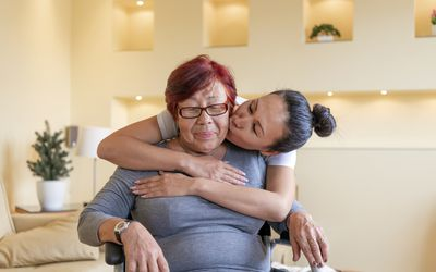 senior woman in wheelchair being carefully embraced by her daughter